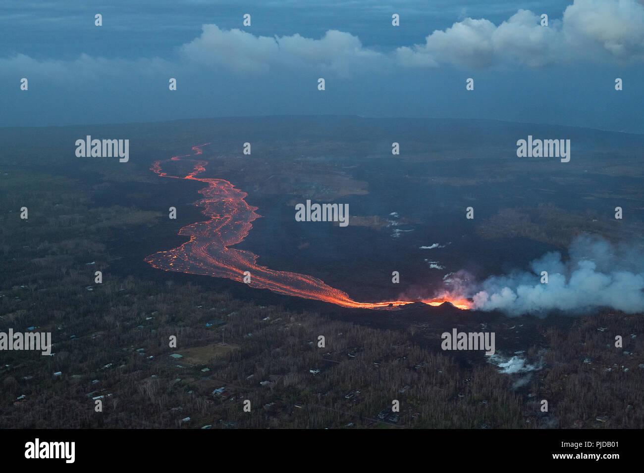 river of hot lava flows from fissure 8 in Kilauea Volcano east rift zone in Leilani Estates subdivision, near Pahoa, toward the sea at Kapoho, Hawaii - Stock Image