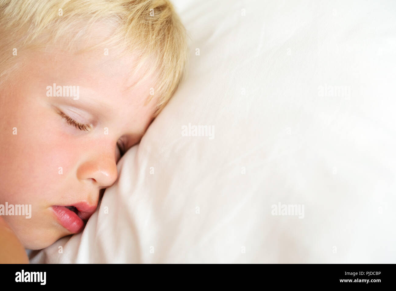 Blondy little boy sleeping on white pillow. Sweet dream concept. Top view. - Stock Image