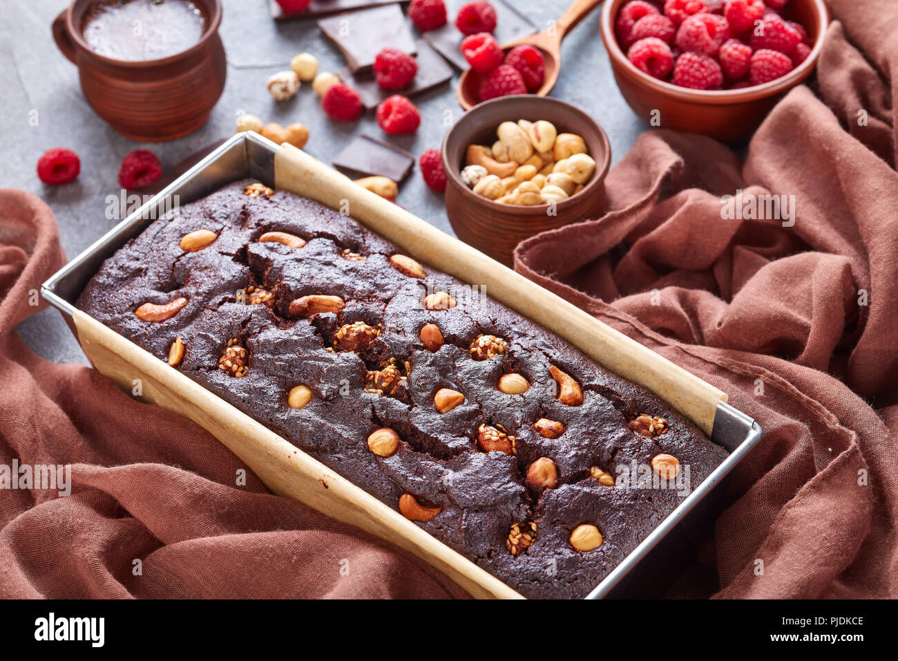 close-up of chocolate buckwheat pound cake with nuts and raspberries in a metal baking mold on a concrete table with cup of coffee and brown tissue, v - Stock Image