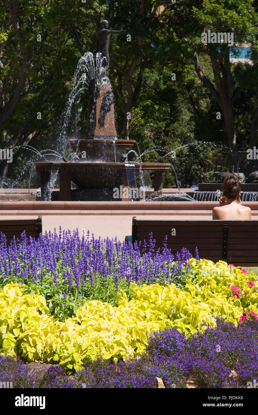 A view of the Archibald Fountain, Hyde Park , Sydney, Australia. The photo also shows colourful flowers and a young woman sitting on a park bench. - Stock Image