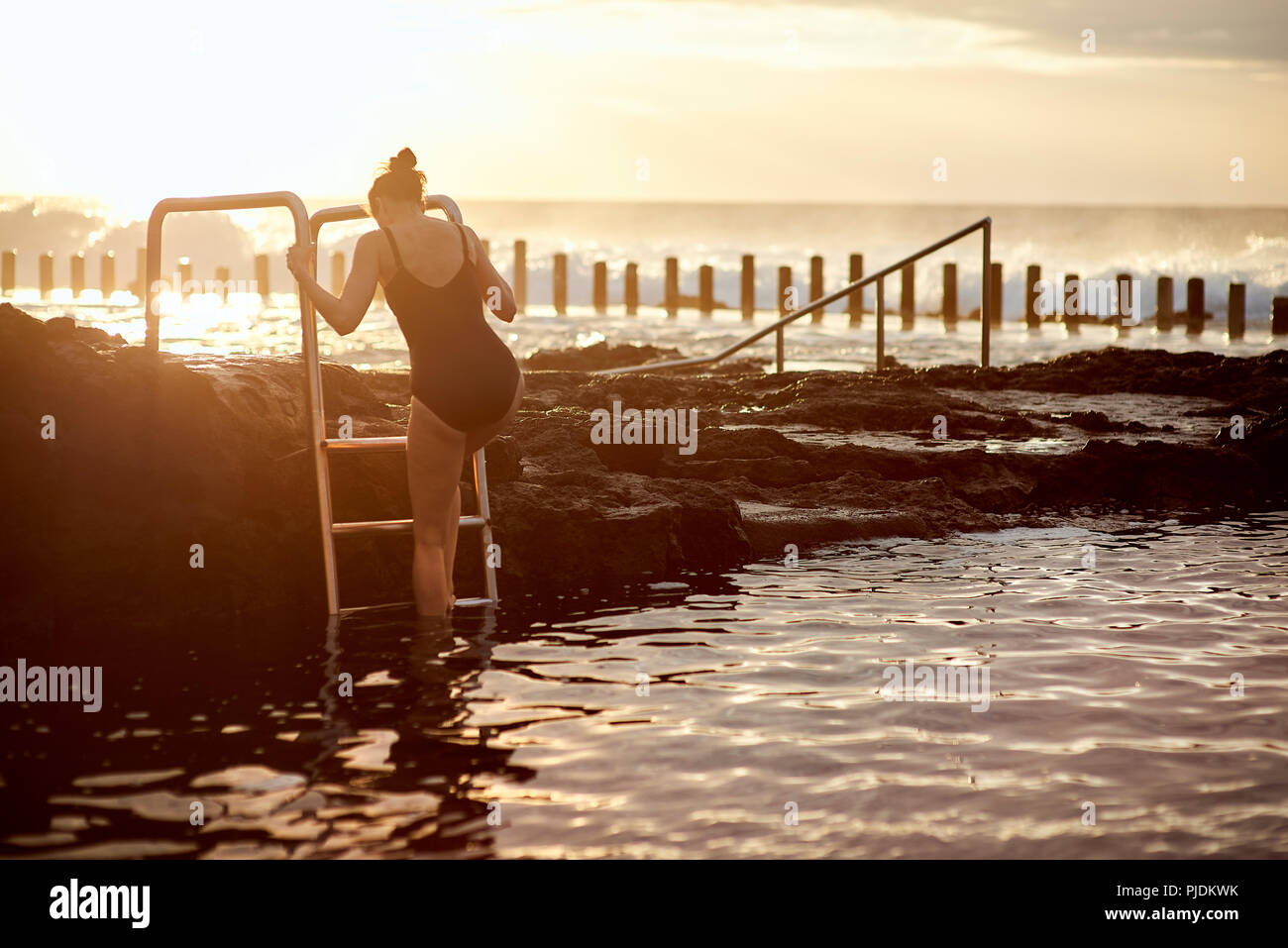 Woman climbing up coastal pool ladder, Las Palmas, Gran Canaria, Canary Islands, Spain - Stock Image