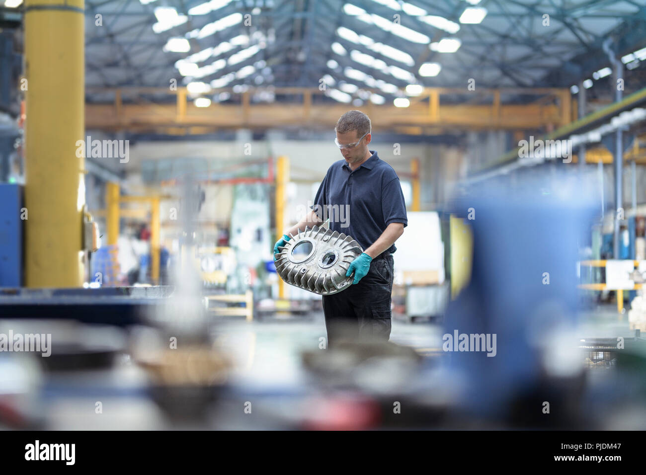 Engineer holding gearbox housing in gearbox factory - Stock Image
