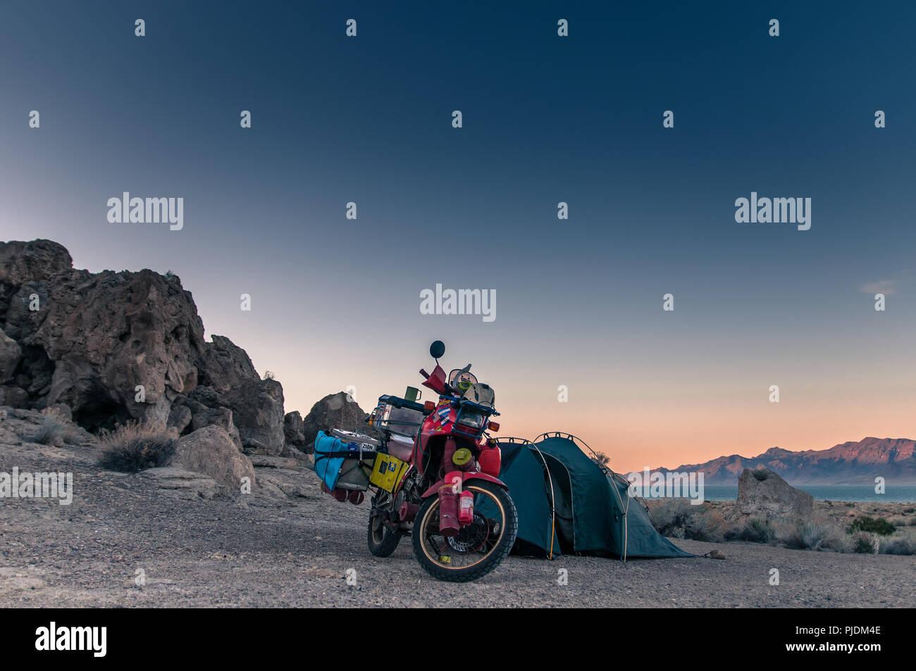 Touring bike parked by tent, Pyramid Lake, Nevada, USA - Stock Image