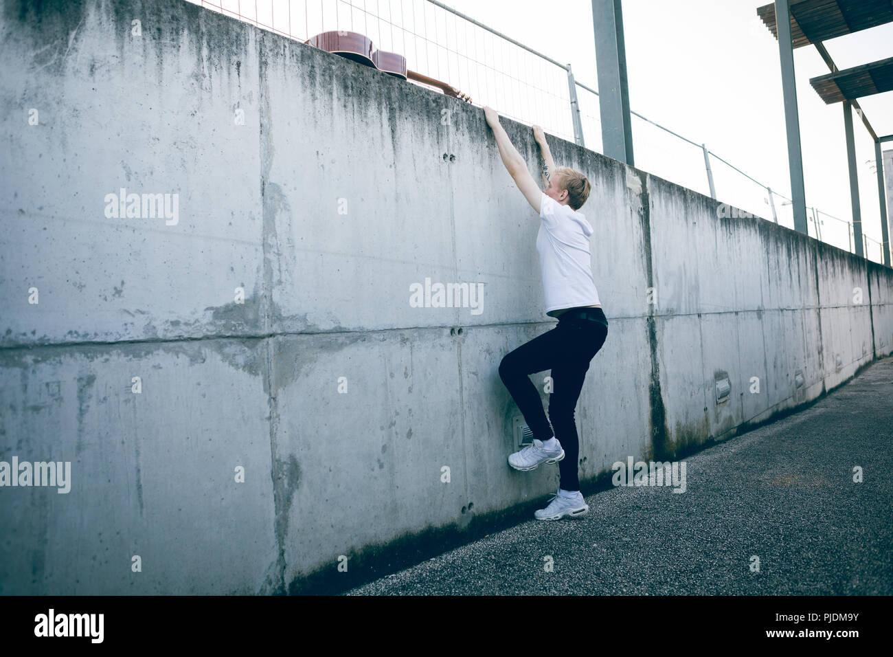 Young musician climbing wall - Stock Image