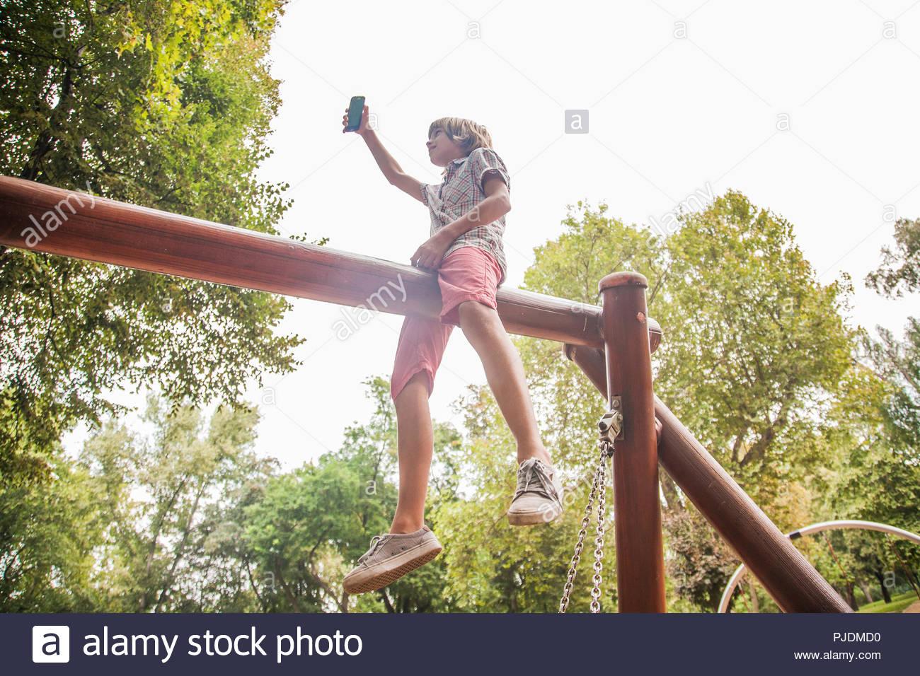 Boy taking selfie on playground equipment - Stock Image