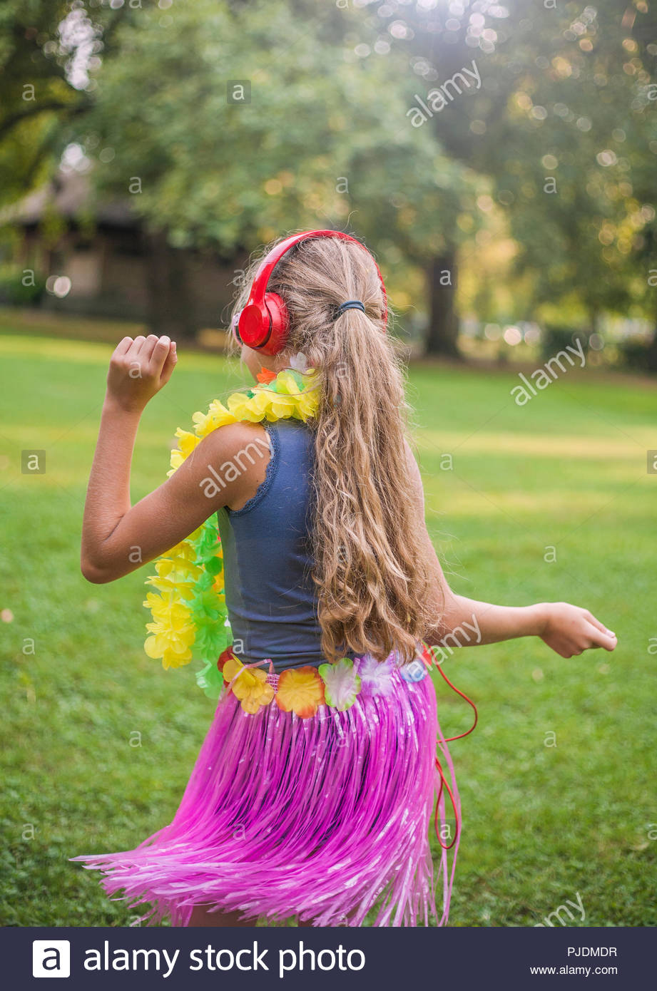 Girl hula dancing in park - Stock Image