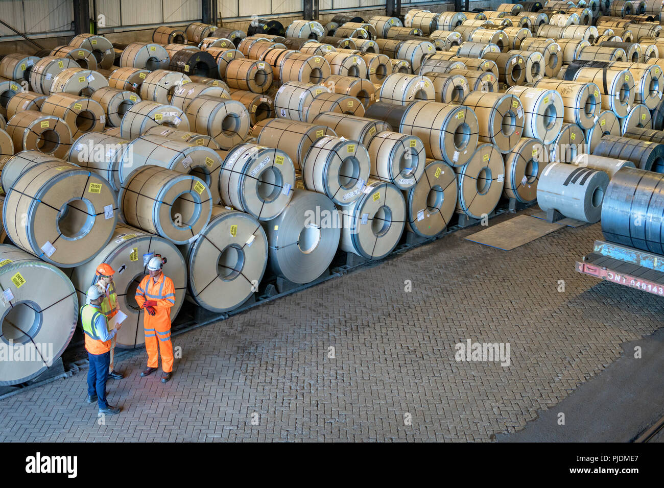 Workers with rows of sheet steel in storage at port - Stock Image