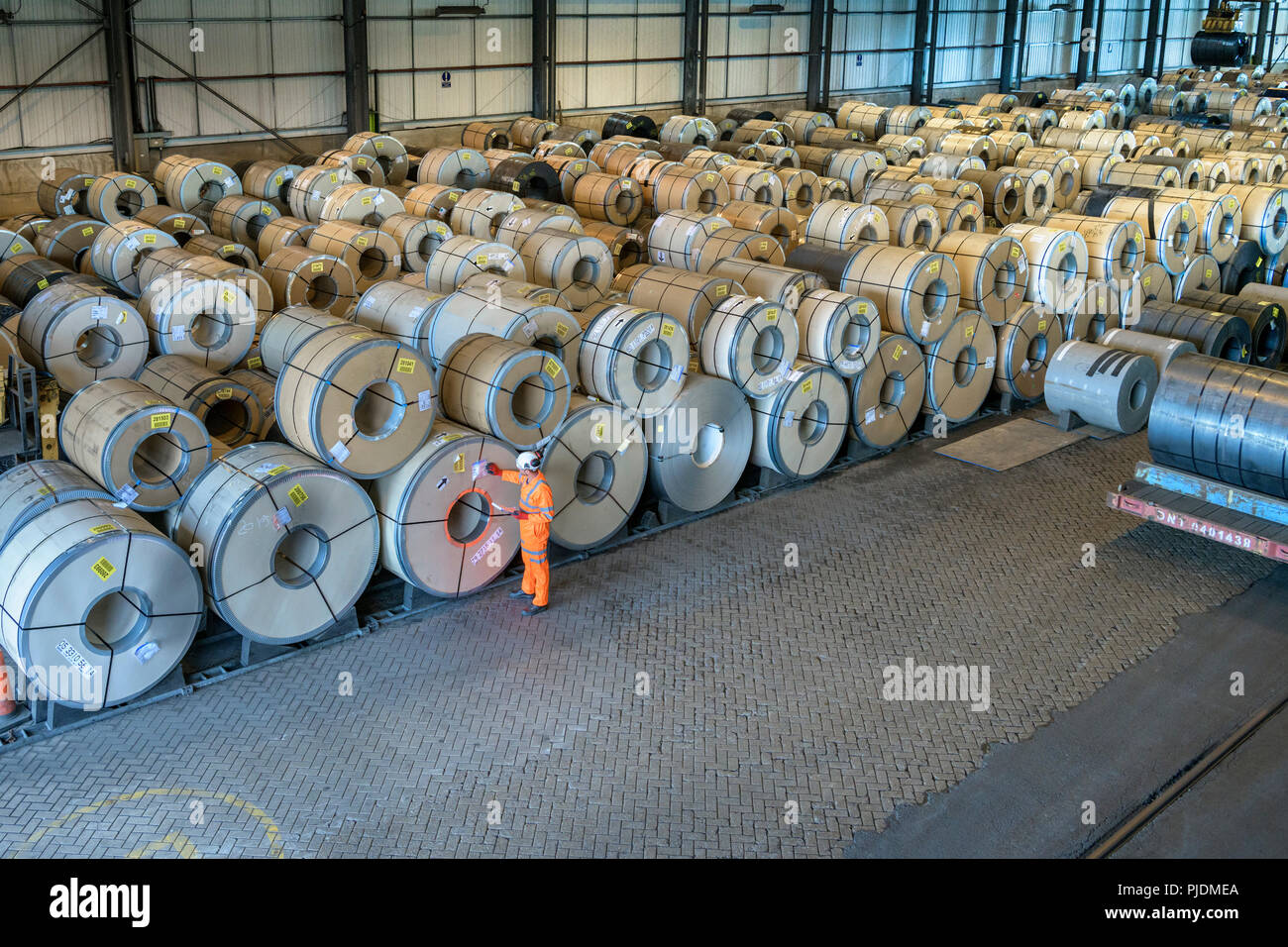 Worker with rows of sheet steel in storage at port - Stock Image