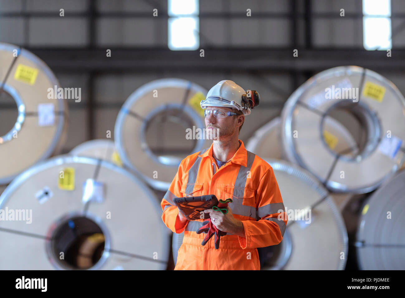Portrait of worker using digital tablet by rows of sheet steel in storage at port - Stock Image