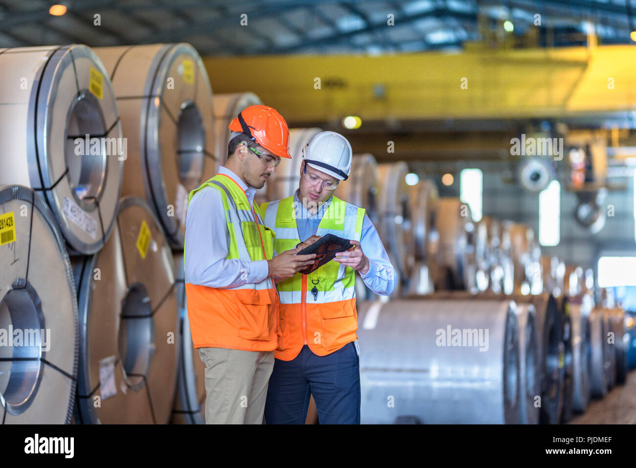 Workers using digital tablet by rows of sheet steel in storage at port - Stock Image