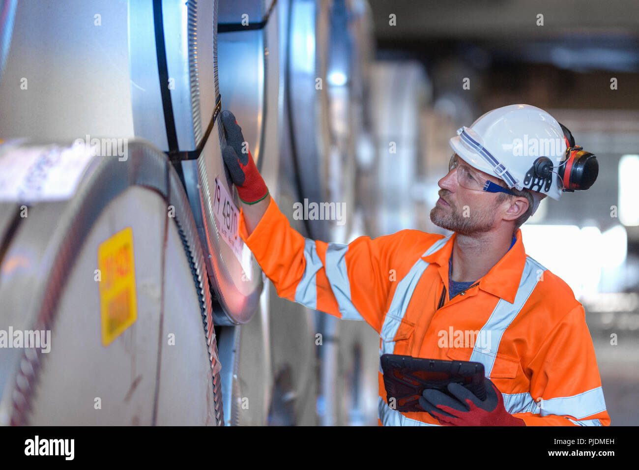 Worker using digital tablet to inspect rows of sheet steel in storage at port - Stock Image