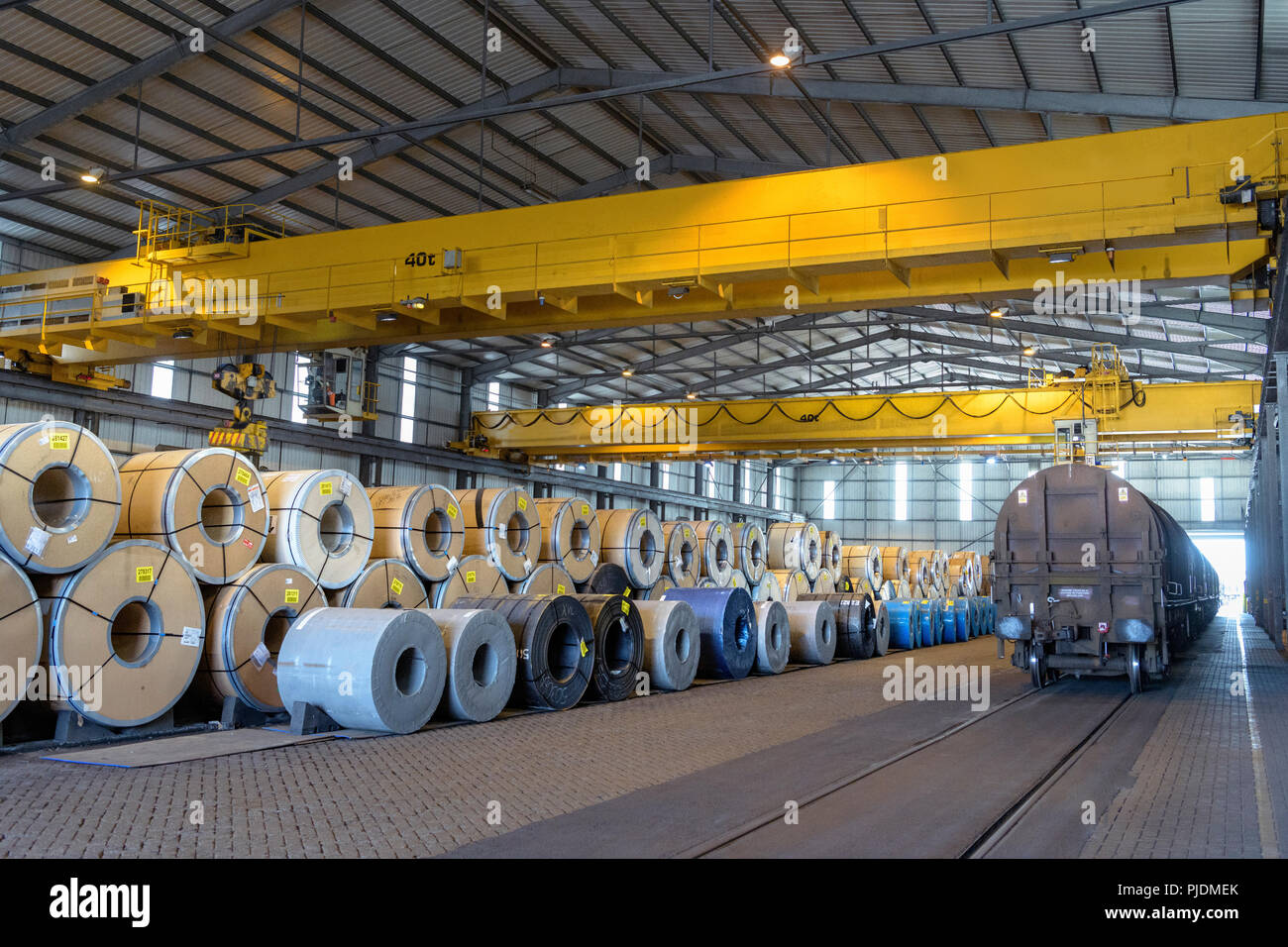 Rows of sheet steel in storage at port - Stock Image