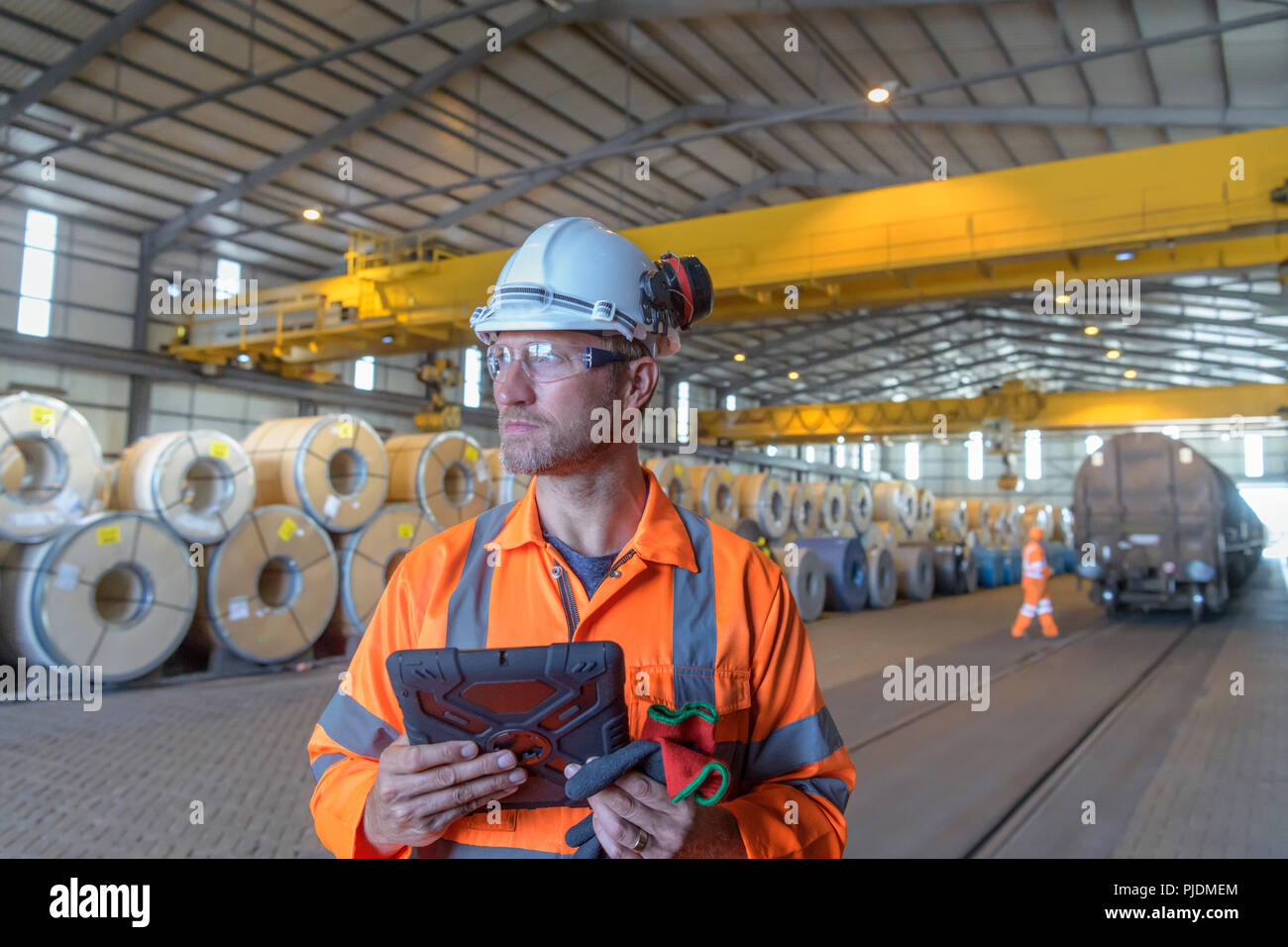 Worker using digital tablet by rows of sheet steel in storage at port - Stock Image