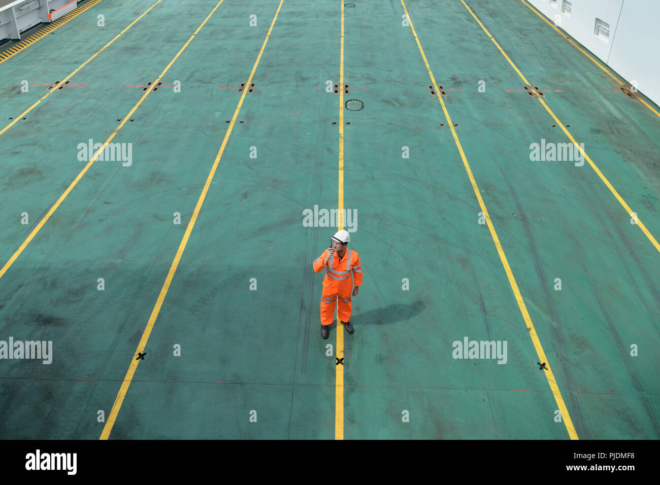 Ship's worker using walkie talkie on deck of ship in port - Stock Image
