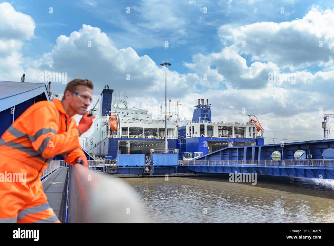 Ship's worker using walkie talkie to communicate with loading ferry ships in port in background - Stock Image