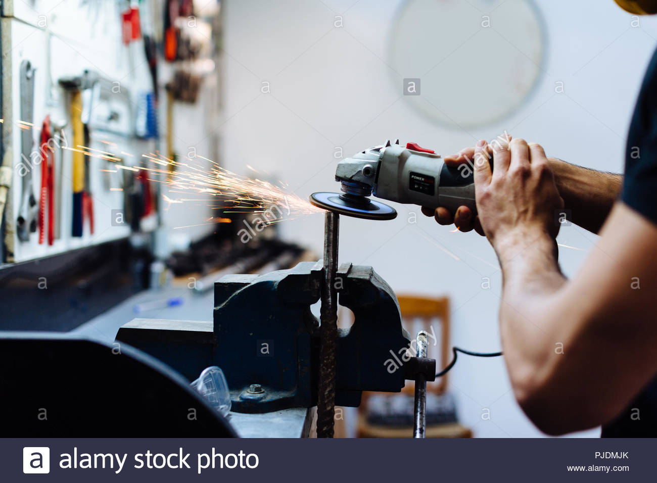Young man using angle grinder on metal in workshop, cropped - Stock Image