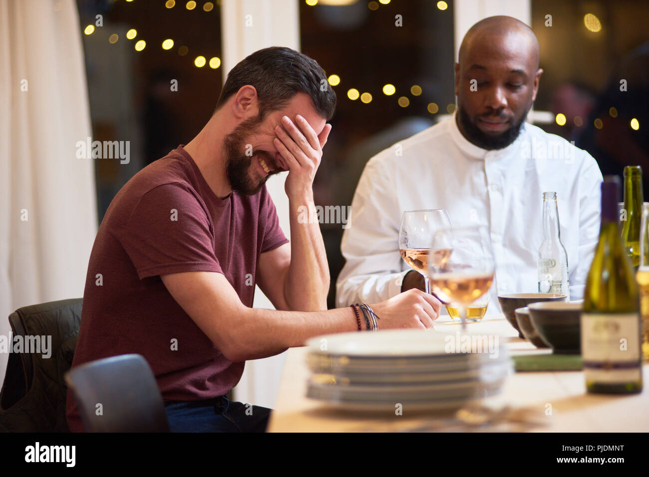 Friend laughing at dinner party - Stock Image