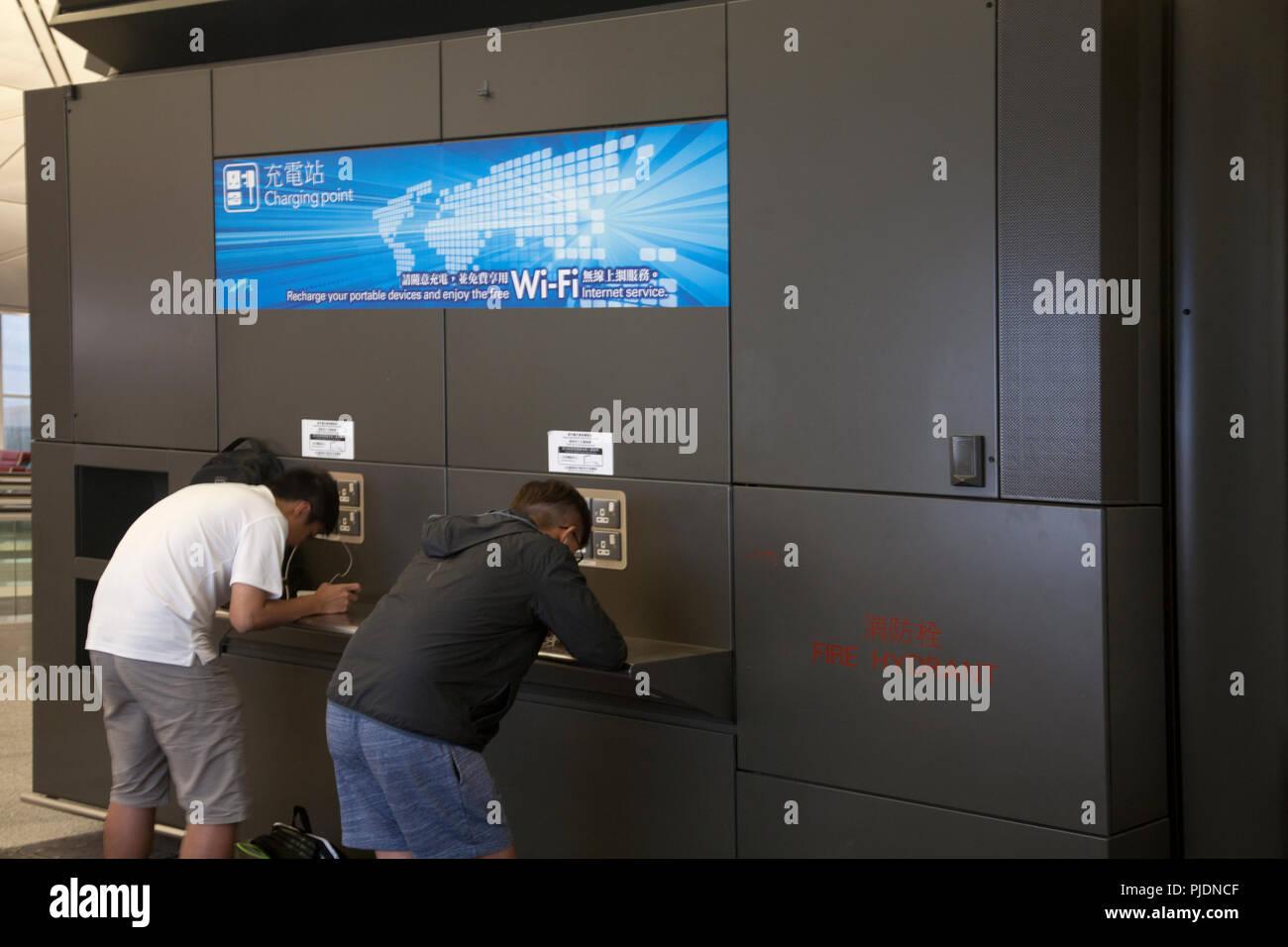 men using electronic devises at charging point terminal 1 hong kong international airport chek lap kok hong kong china - Stock Image