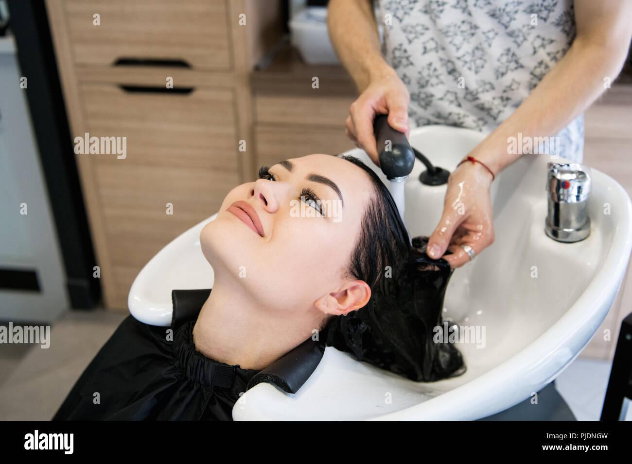 Beautiful young girl enjoying hair washing in hairdressing salon. - Stock Image