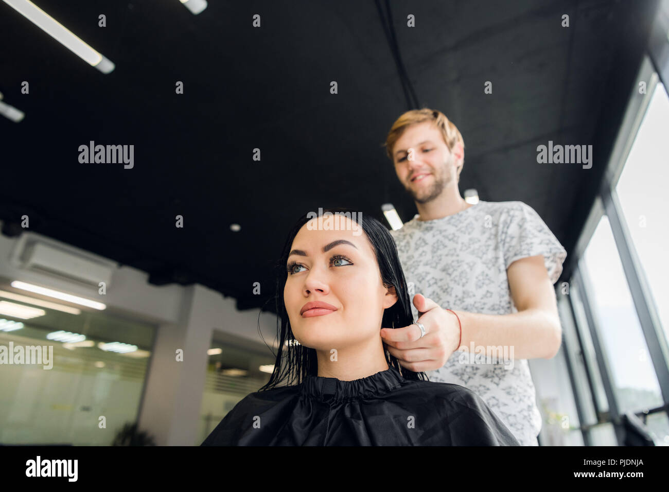 Happy young brunette woman and hairdresser preparing for haircut or hairstyle at beaty salon - Stock Image