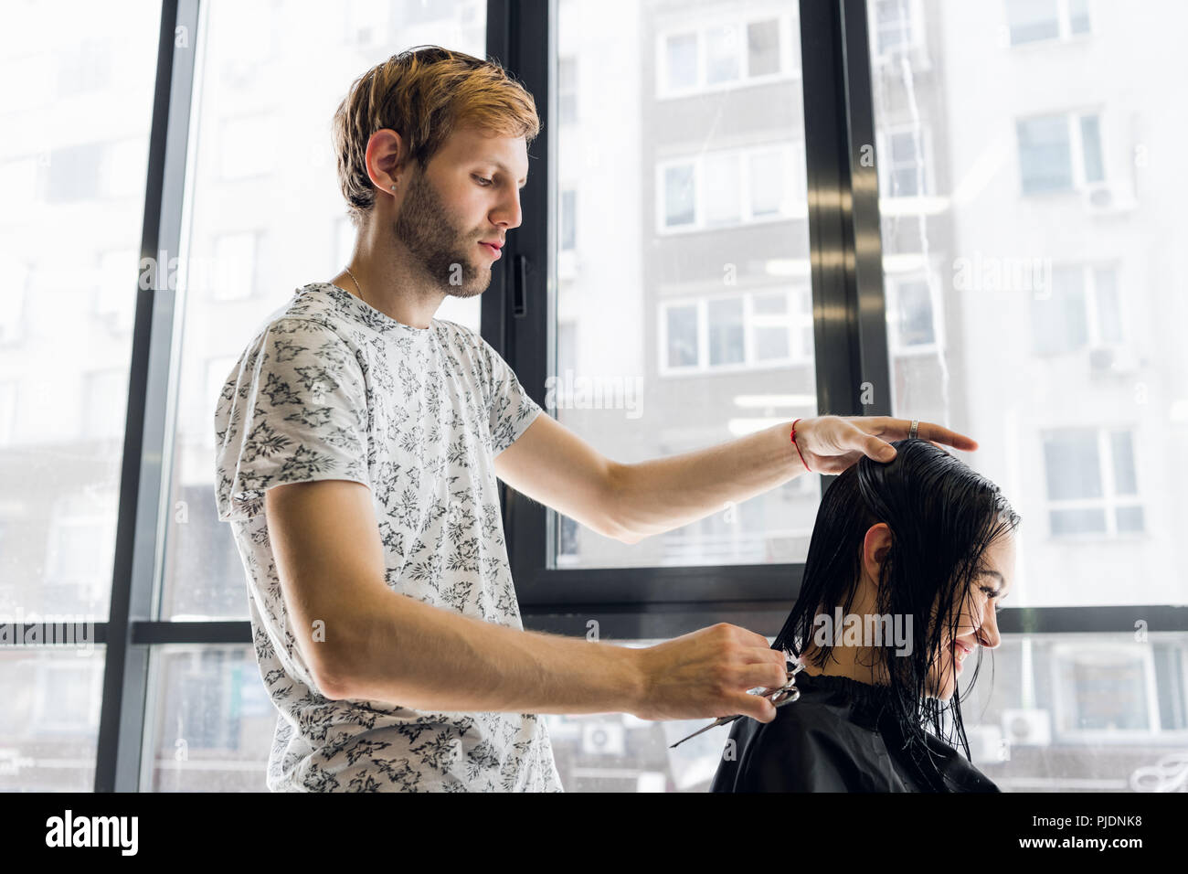 The hairdresser does a haircut with scissors of hair to a young girl in a beauty salon. - Stock Image