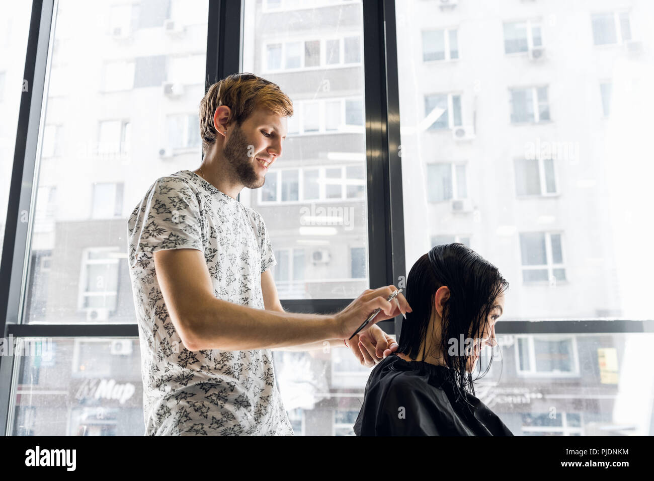 Funny story. Delighted cheerful woman laughing while hairdresser telling a funny story to her - Stock Image