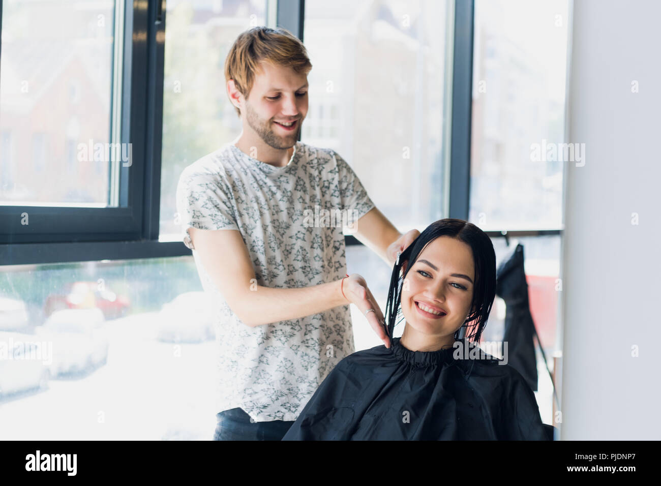Male hairdresser smiling and talking with a customer while making a new haircut to beutiful young brunette woman - Stock Image