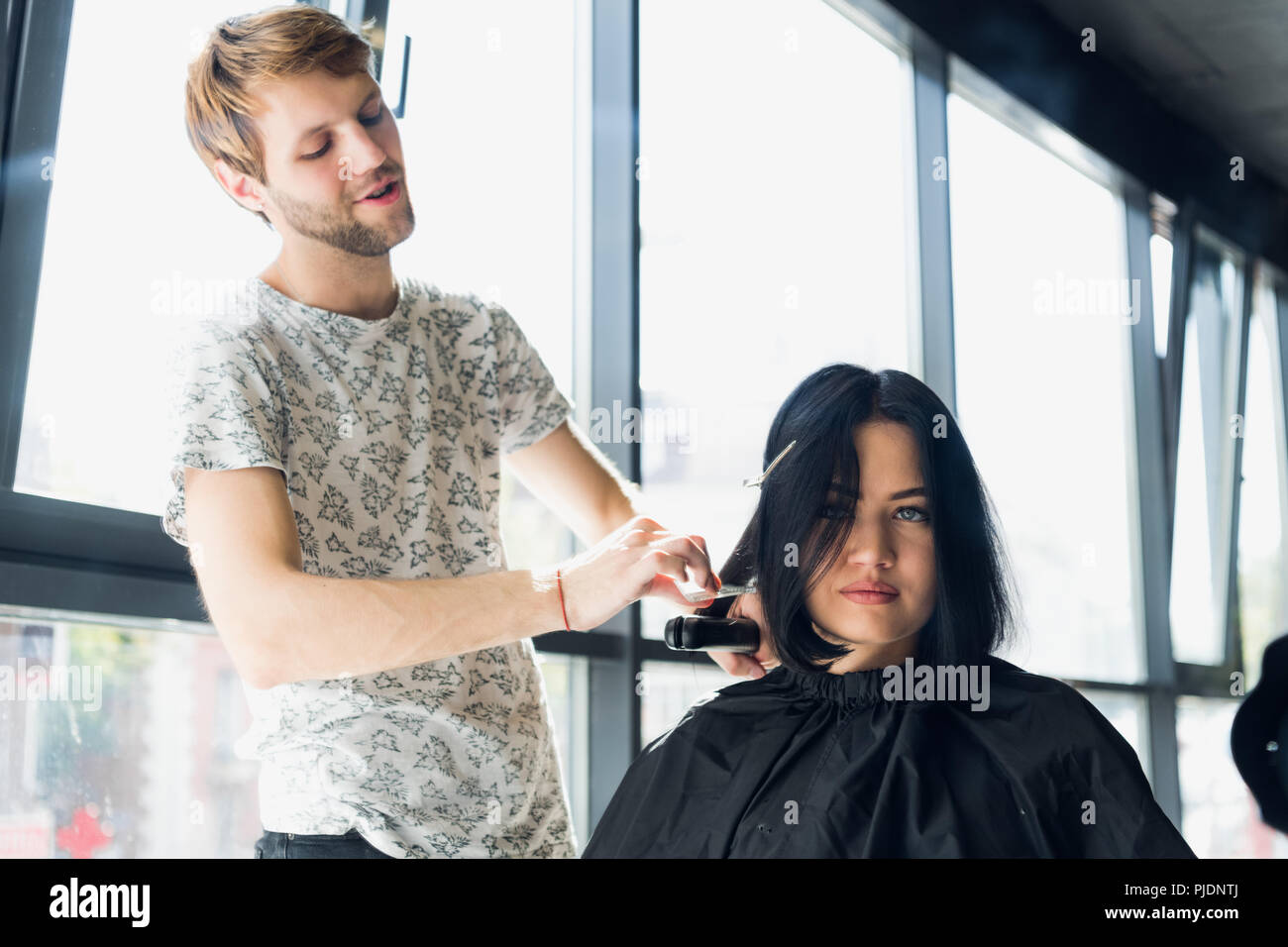 Close up. Female hairdresser straighten brown hair to woman using hair iron in beauty salon. Female stylist makes hairstyle for young beautiful woman in hairdressing salon. - Stock Image