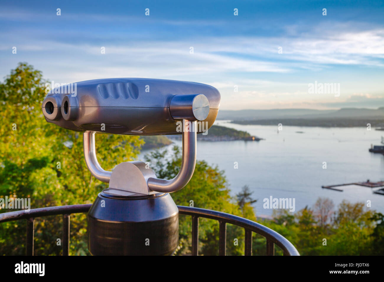 Tourist binocular telescope at the Ekeberg hill overlooking Oslo cityscape at sunset - travel in Norway concept - Stock Image