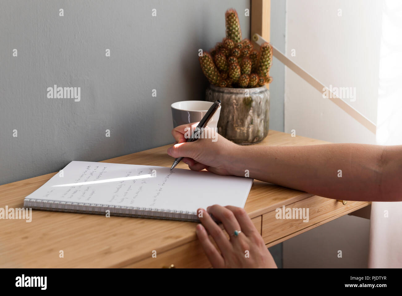 Light slicing perfectly onto girl writing in notebook. - Stock Image