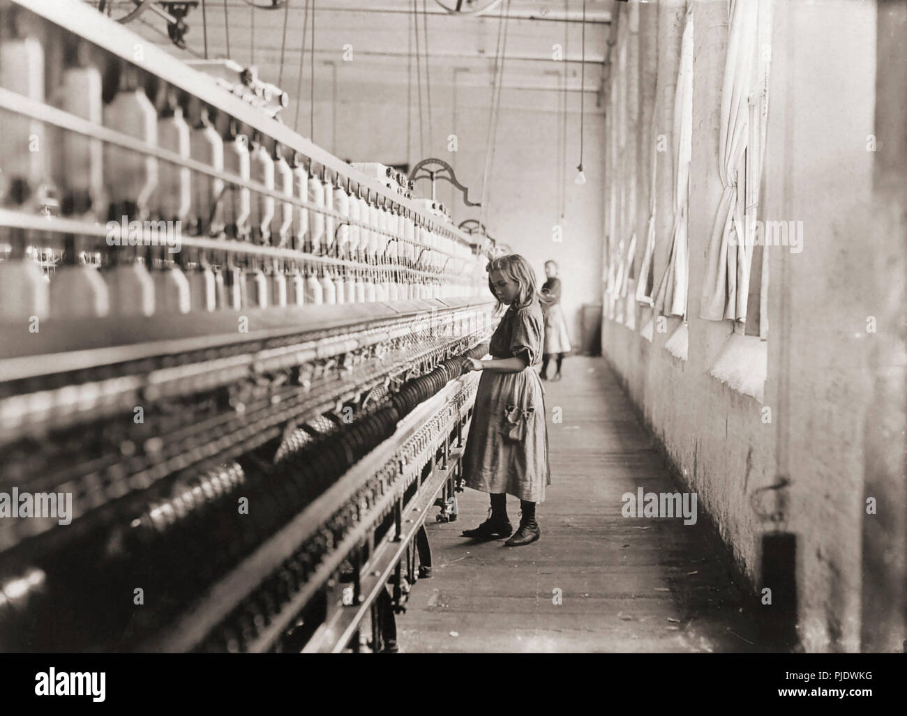 Sadie Pfeiffer, Spinner in a Cotton Mill.  Taken in Lancaster, North Carolina in 1908. After a photograph by Lewis Hine, 1874-1940.  Hine was a sociology teacher who used photography to record social problems and spur reform. - Stock Image