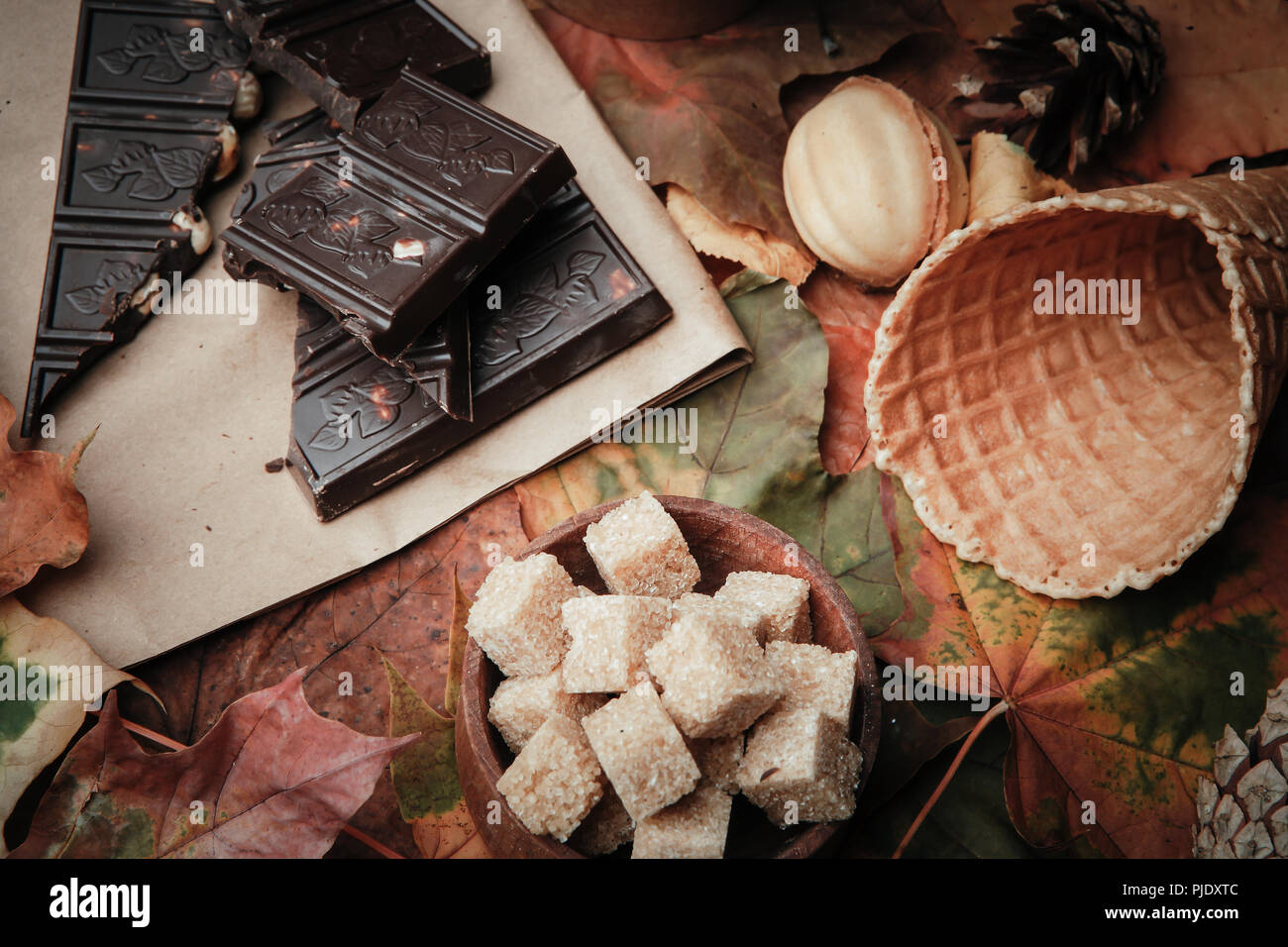 Various sweets on leaves in autumn park - Stock Image