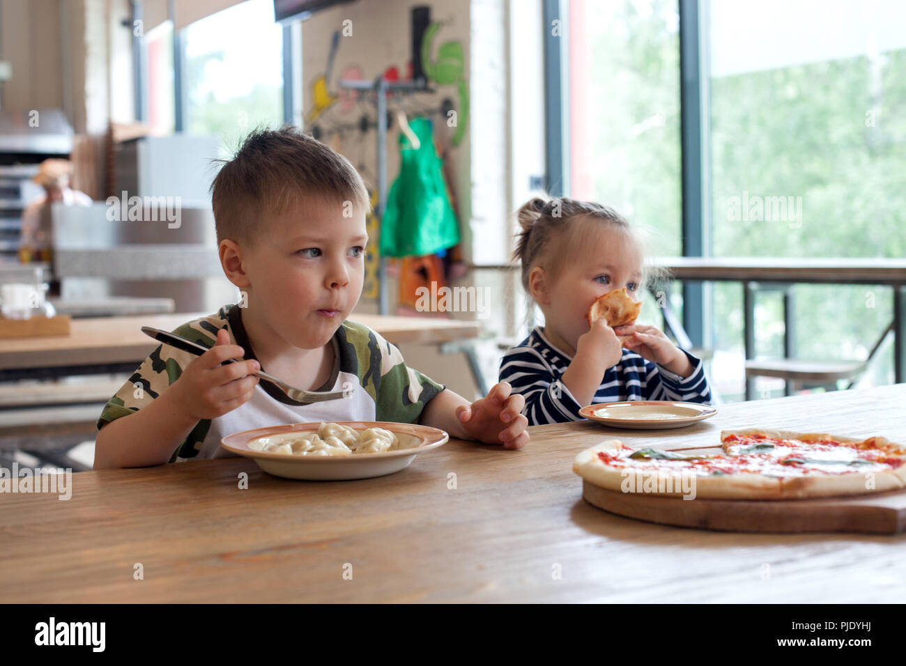 kids eat pizza and meat dumplings at cafe. children eating unhealthy food indoors. Siblings in the cafe, family holiday concept. - Stock Image