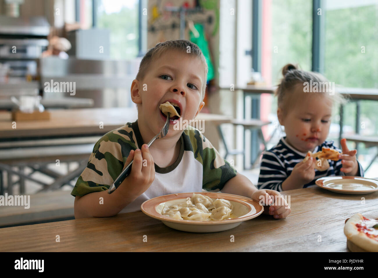 kids eat pizza and meat dumplings at cafe. children eating unhealthy food indoors. Siblings in the cafe, family holiday concept. Stock Photo