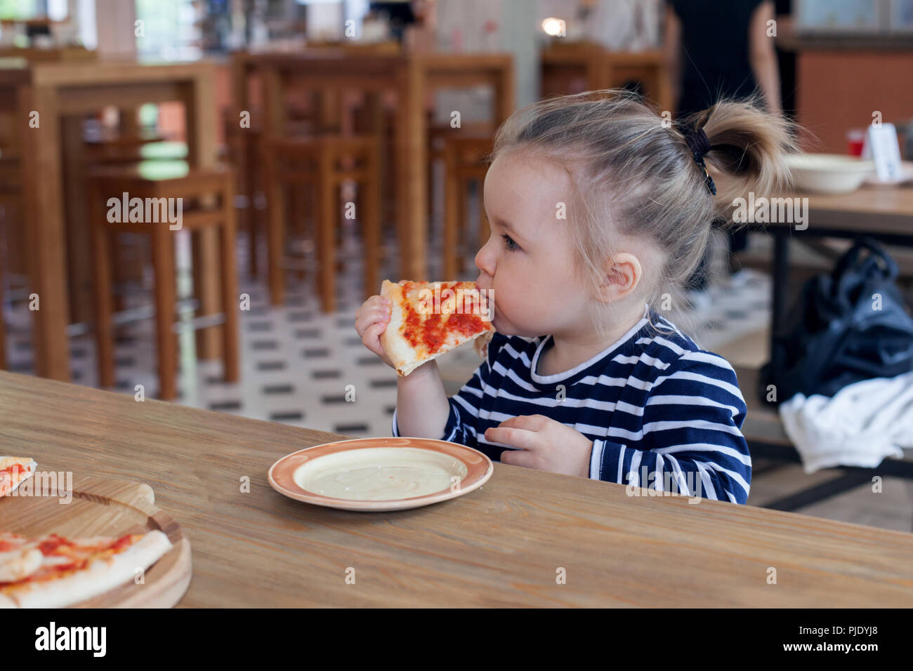 Cute little 2 years girl eating pizza in the restaurant Stock Photo