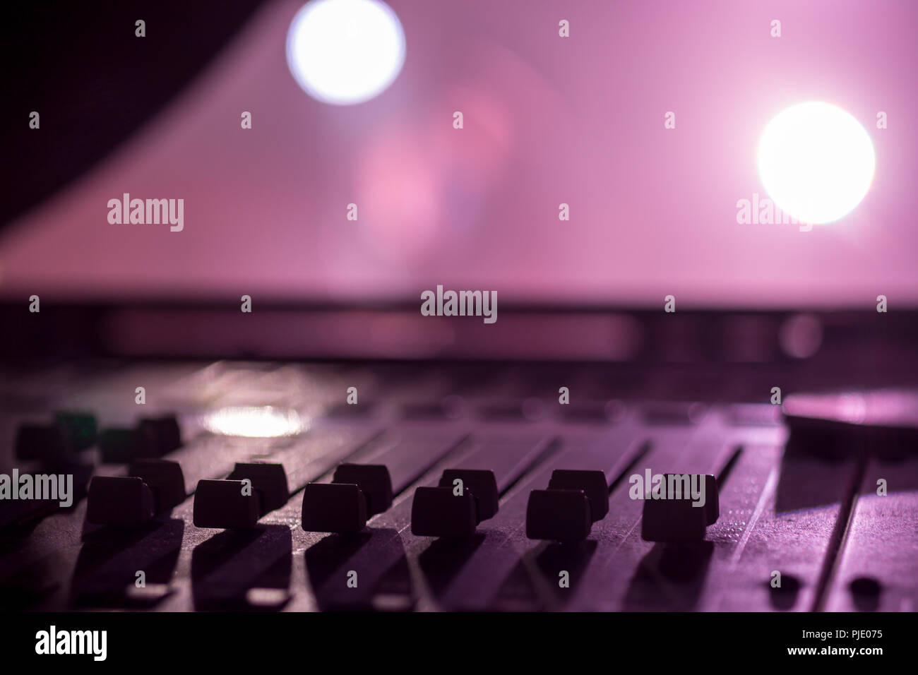 Stage side Low level view of Faders on a Professional Audio Sound Mixing Console at music festival, black Faders and pink purple background - Stock Image