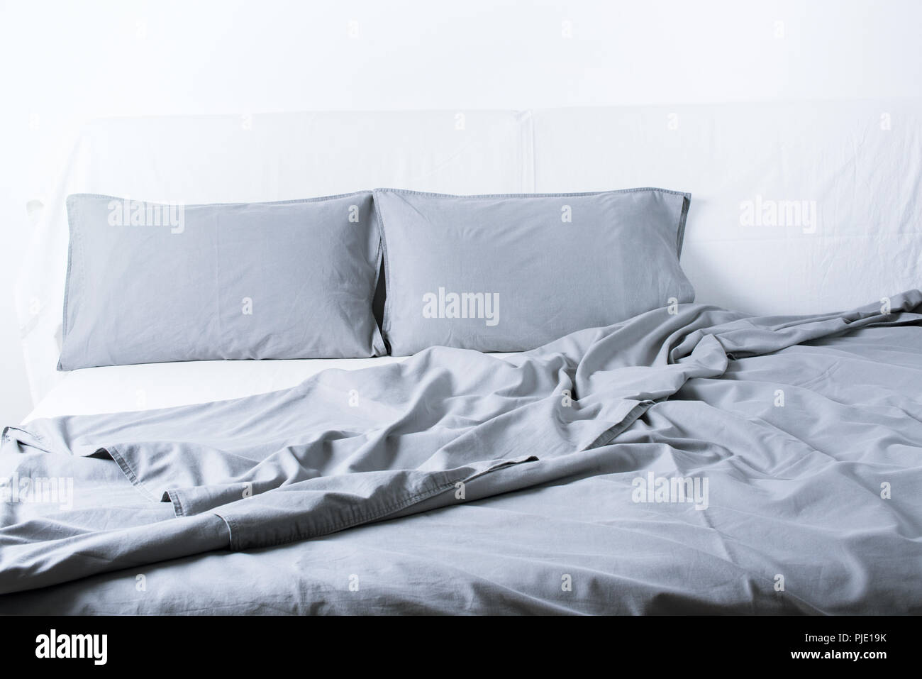 Close Up Grey Linens Bedding Sheet Pillow Coverlet White Wall Room Background Messy Bed Concept Interior - Stock Image