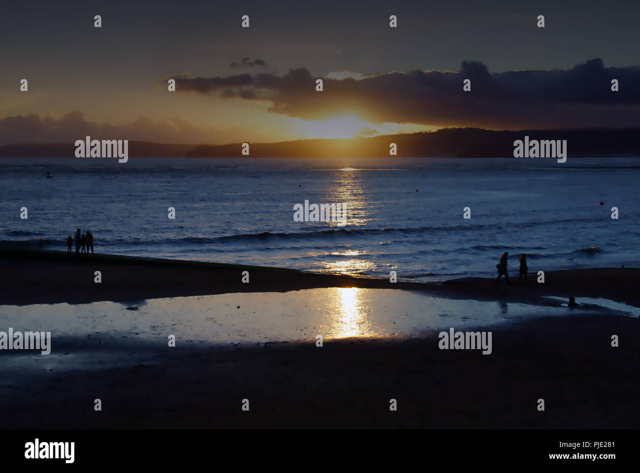 A winter sunset on a calm day at Exmouth beach in Devon, England, a family enjoy a last walk at sunset - Stock Image