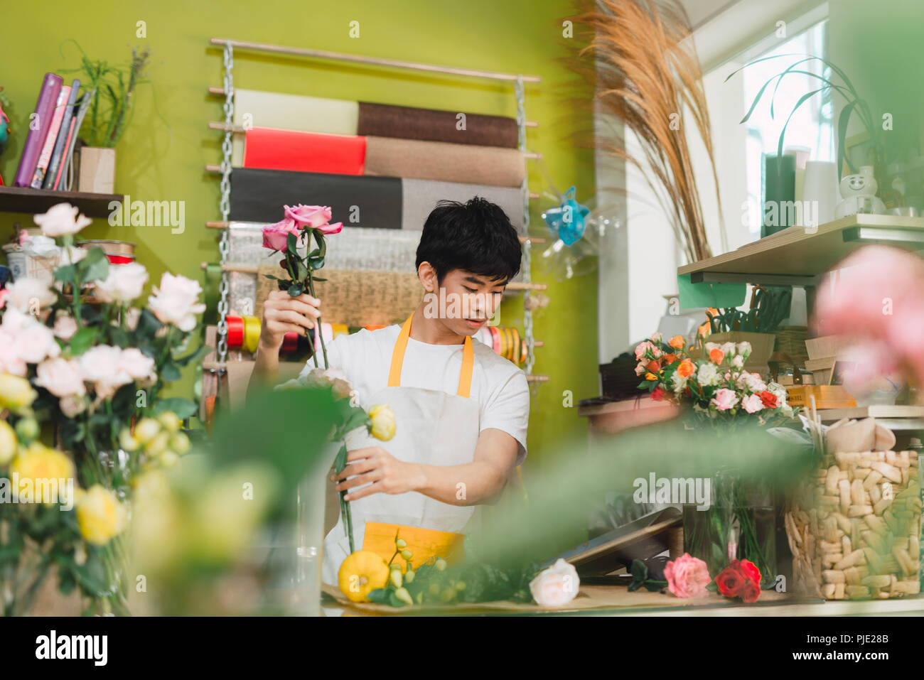Small business. Male florist making rose bouquet at counter desk in flower shop. Man assistant or owner in floral design studio, making decorations an - Stock Image