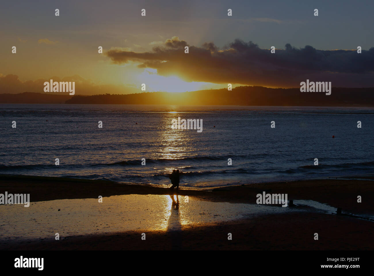 The last walk of the day at sunset, for a couple, in winter on Exmouth Beach in Devon England - Stock Image