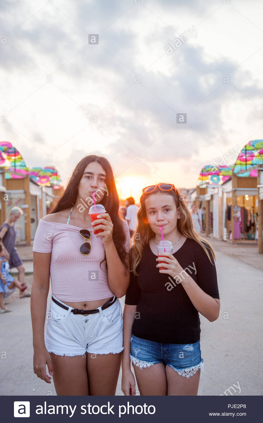 Two teenage girls stroll through an open-air market and have a refreshing red drink. - Stock Image