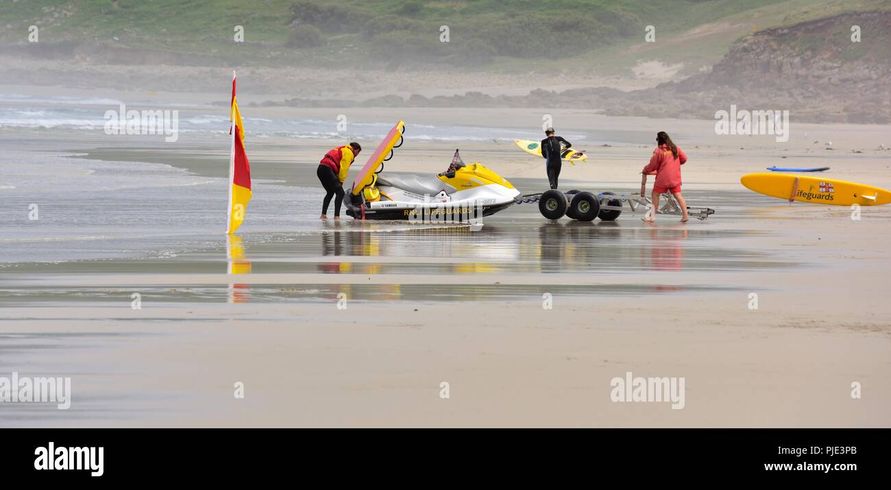 RNLI Lifeguards with a rescue jet ski on Sennen Cove Beach,Cornwall,England,UK - Stock Image
