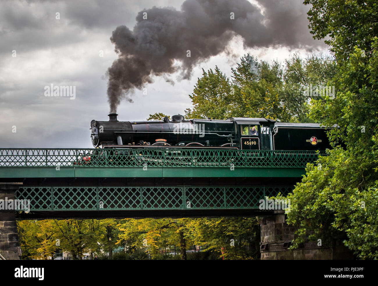 The 45690 Leander steam locomotive hauling The Scarborough Spa Express over the River Ouse in York, as the trees begin to change colour ahead of Autumn. - Stock Image