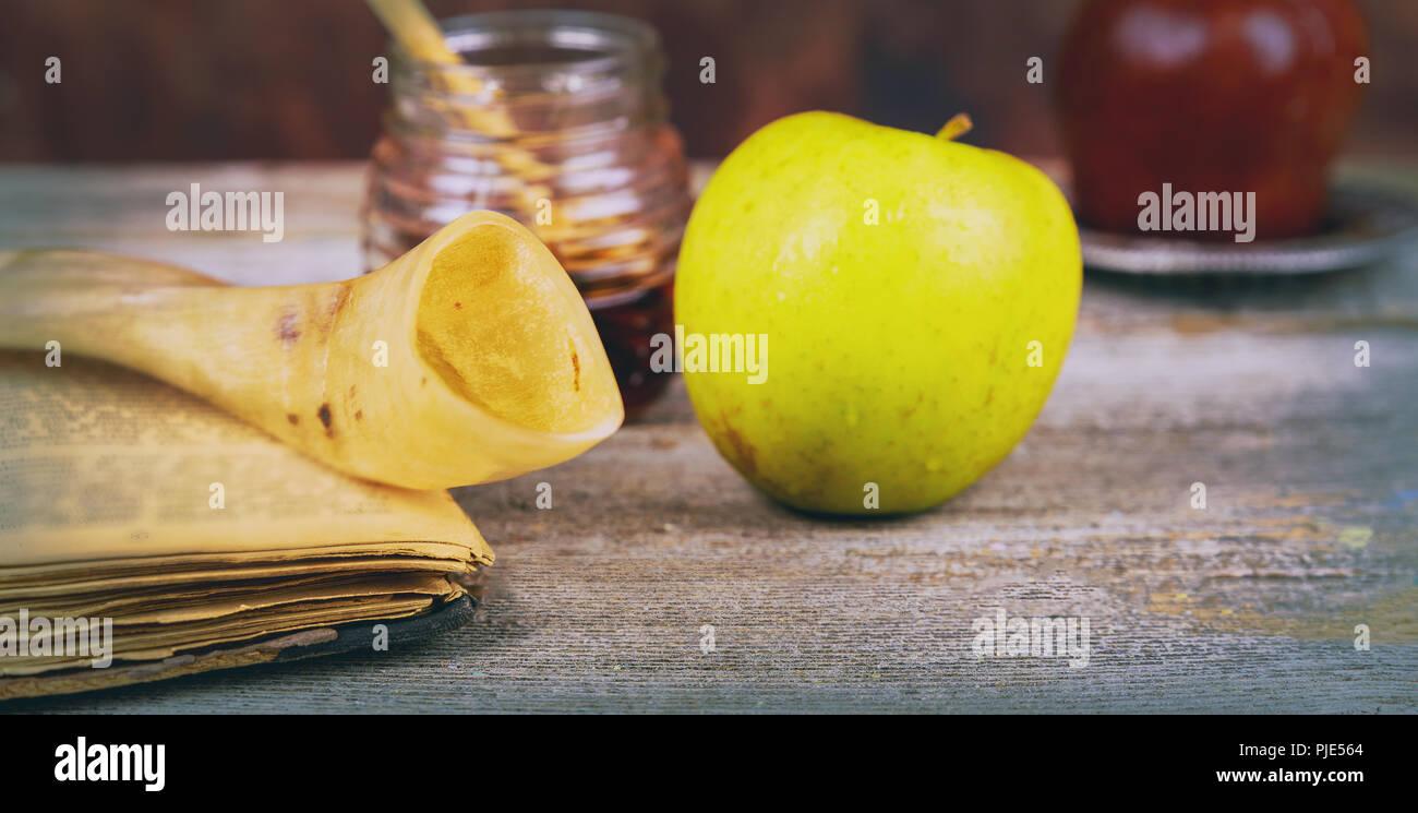 Honey and pomegranate for traditional holiday symbols rosh hashanah jewesh holiday on wooden table top and shofar torah book and a kippah a yamolka - Stock Image