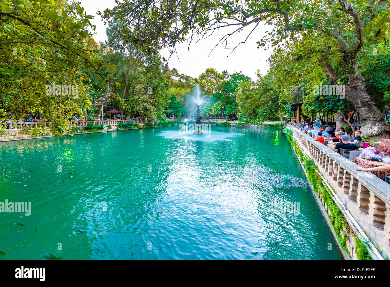 Unidentified people sit around Aynzeliha Lake,second sacred pool within Golbasi Park in Sanliurfa.Turkey.18 July 2018 - Stock Image