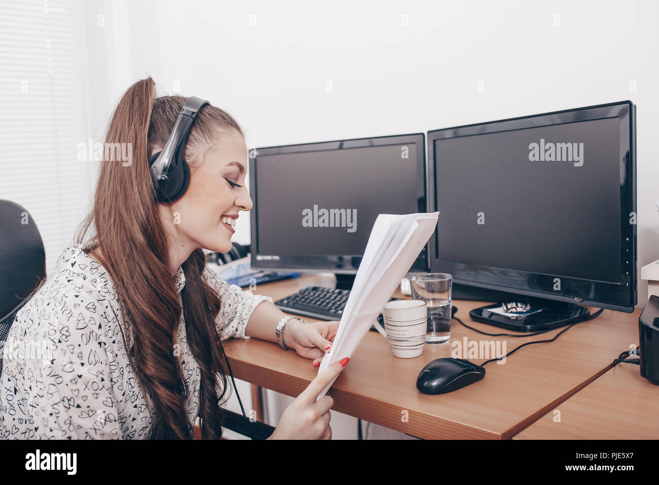 Young friendly operator female agent with headsets working in a call centre Stock Photo
