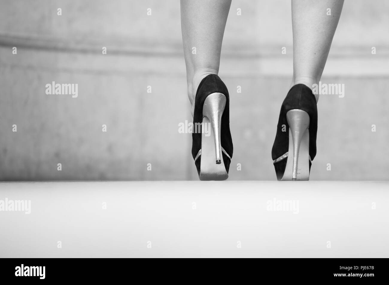 Rear view of lady's ankles in a smart pair of high heeled black and silver shoes. - Stock Image