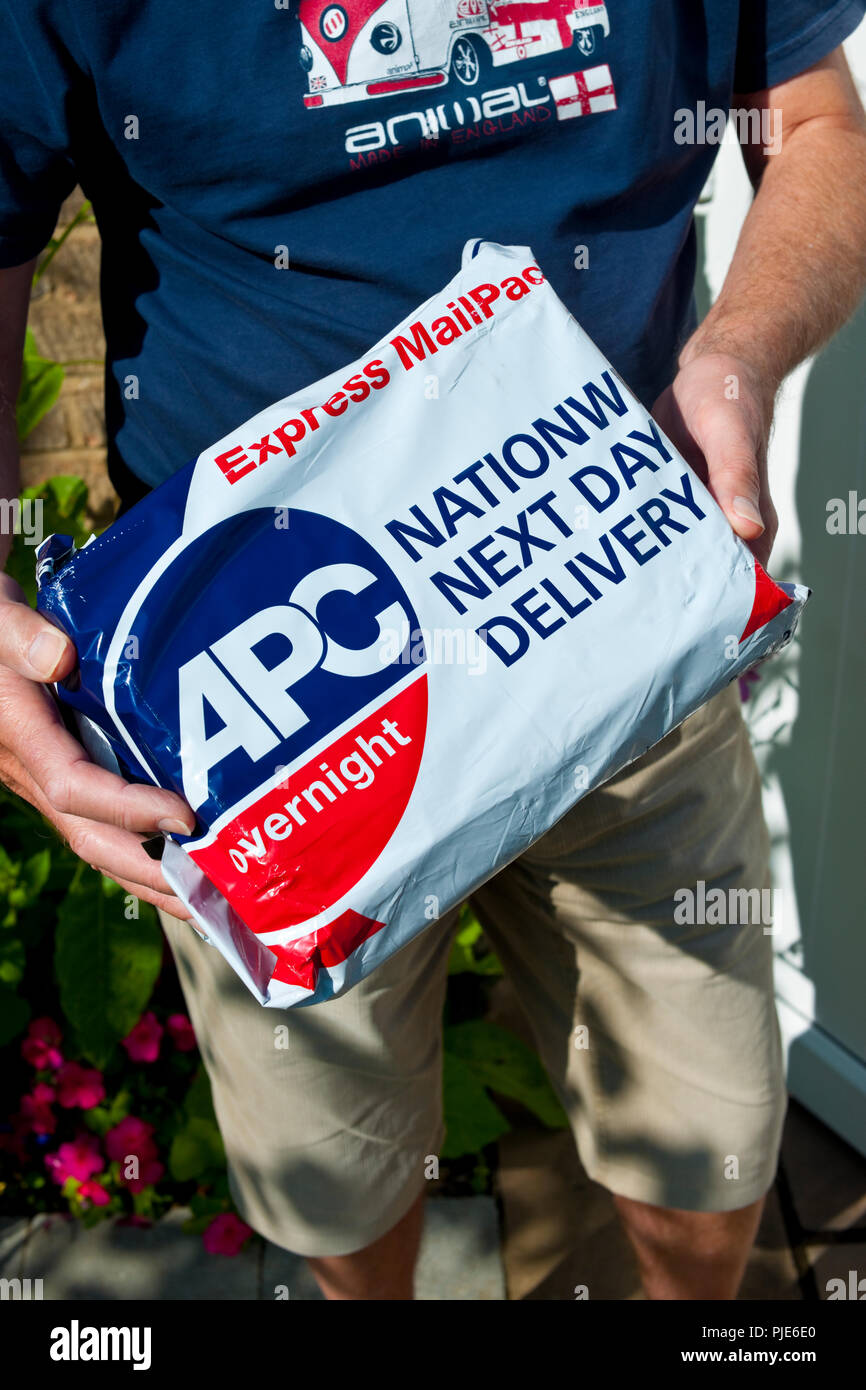 Courier delivering APC overnight express mail parcel England UK United Kingdom GB Great Britain - Stock Image
