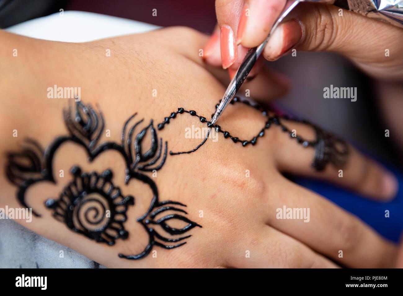 7cf587e68 Woman painting black henna tattoo on a girl's hand Stock Photo ...