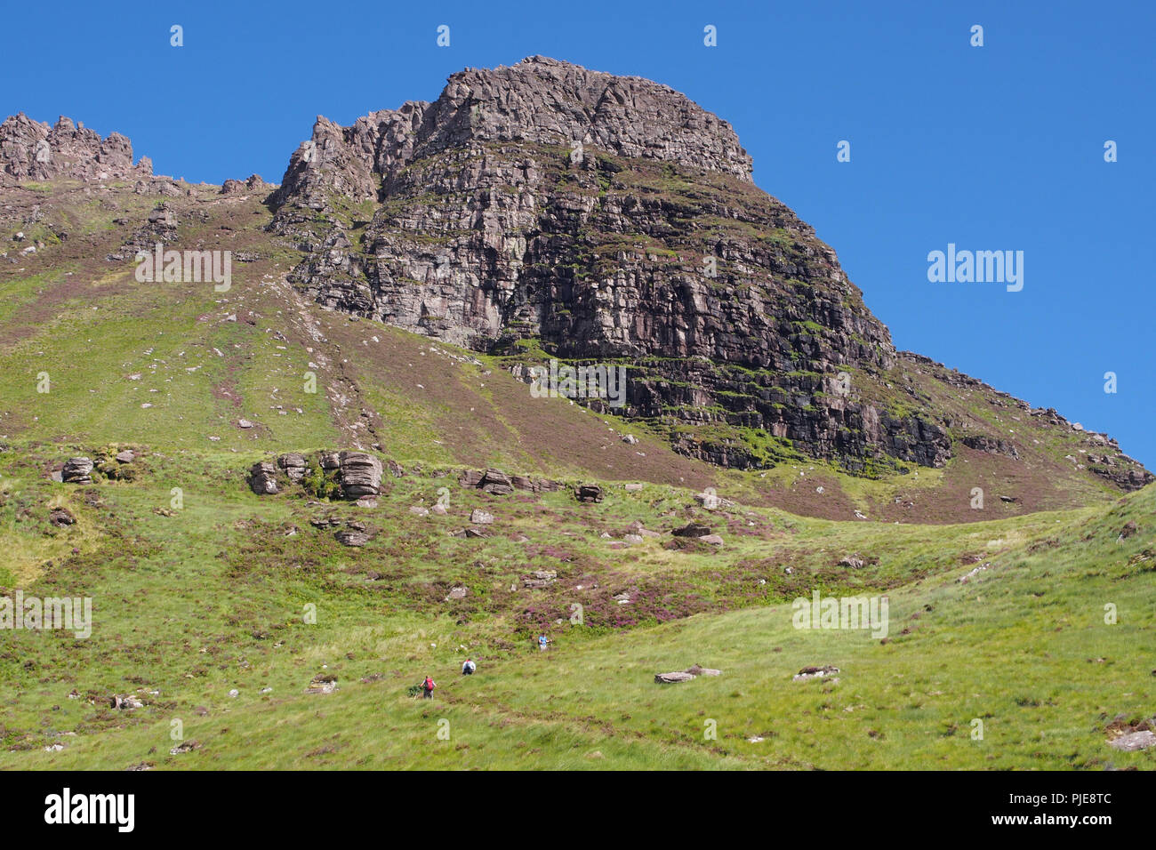 A view looking up at Stac Pollaidh, Scotland, from the south side, car park path, with three hill walkers ascending the mountain track to the rocks - Stock Image